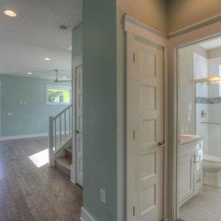 Modelo de cuarto de baño marinero con lavabo bajoencimera, armarios estilo shaker, puertas de armario blancas, encimera de ónix, ducha abierta, sanitario de una pieza, baldosas y/o azulejos azules, baldosas y/o azulejos de vidrio, paredes grises y suelo de baldosas de cerámica