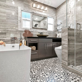 Small beach style master gray tile and porcelain tile cement tile floor and multicolored floor bathroom photo in Los Angeles with flat-panel cabinets, black cabinets, a bidet, gray walls, a vessel sink, quartz countertops and black countertops