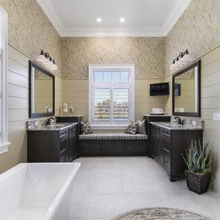Large coastal master ceramic floor and beige floor bathroom photo in Orlando with dark wood cabinets, beige walls, an undermount sink, shaker cabinets and a hinged shower door