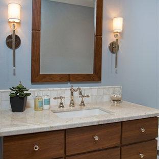 サンディエゴの中サイズのトランジショナルスタイルのおしゃれなバスルーム (浴槽なし) (フラットパネル扉のキャビネット、中間色木目調キャビネット、アルコーブ型シャワー、一体型トイレ、ベージュのタイル、青い壁、オーバーカウンターシンク、セラミックタイル、珪岩の洗面台、ライムストーンの床) の写真