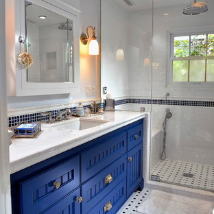 Example of a beach style 3/4 black and white tile and ceramic tile mosaic tile floor and multicolored floor alcove shower design in Orange County with white walls, recessed-panel cabinets, blue cabinets, an undermount sink, tile countertops and a hinged shower door