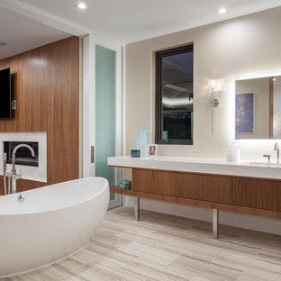 Modelo de cuarto de baño principal, contemporáneo, extra grande, con armarios con paneles lisos, puertas de armario de madera oscura, bañera exenta, paredes blancas, lavabo integrado, encimera de cuarzo compacto, suelo multicolor y encimeras blancas