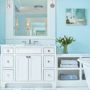 Foto de cuarto de baño principal, costero, con armarios tipo mueble, puertas de armario blancas, bañera exenta, baldosas y/o azulejos blancos, paredes azules, suelo de baldosas de cerámica, lavabo encastrado y encimera de granito