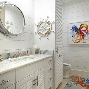 Immagine di una stanza da bagno per bambini costiera con ante a persiana, ante bianche, pareti bianche, lavabo sottopiano e pavimento beige
