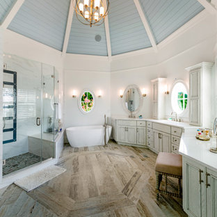 Inspiration for a coastal master medium tone wood floor, brown floor, double-sink, exposed beam, shiplap ceiling and vaulted ceiling bathroom remodel in Baltimore with recessed-panel cabinets, gray cabinets, white walls, an undermount sink, a hinged shower door, white countertops and a built-in vanity