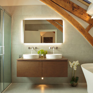 Inspiration for a rural ensuite bathroom in Other with flat-panel cabinets, medium wood cabinets, a freestanding bath, grey tiles, grey walls, a vessel sink, wooden worktops, grey floors, a sliding door and brown worktops.
