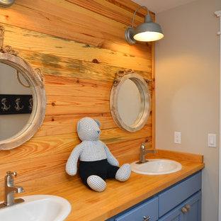 Modelo de cuarto de baño infantil, campestre, de tamaño medio, con paredes beige, lavabo encastrado, armarios estilo shaker, puertas de armario azules y encimera de madera