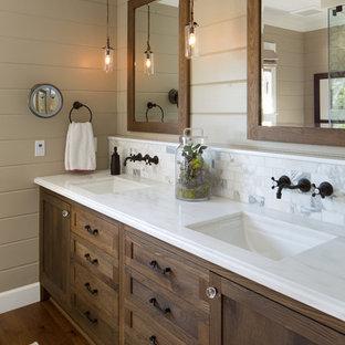 Создайте стильный интерьер: ванная комната в стиле кантри с темными деревянными фасадами, коричневыми стенами, белой плиткой, каменной плиткой и белой столешницей - последний тренд