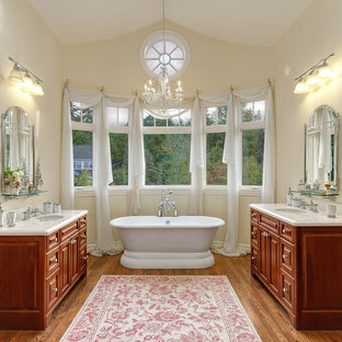 Example of a large coastal master medium tone wood floor freestanding bathtub design in Seattle with raised-panel cabinets, medium tone wood cabinets, quartzite countertops and yellow walls