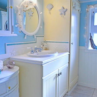 Foto de cuarto de baño con ducha, costero, pequeño, con armarios con paneles empotrados, puertas de armario amarillas, baldosas y/o azulejos blancos, baldosas y/o azulejos de cerámica, paredes azules, suelo vinílico, lavabo encastrado, encimera de azulejos y suelo beige