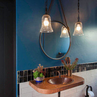 Example of a small eclectic black and white tile and ceramic tile terra-cotta floor and red floor alcove shower design in San Diego with a one-piece toilet, blue walls, a drop-in sink, copper countertops and a hinged shower door