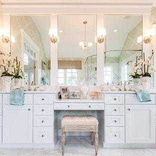 Bild på ett stort maritimt en-suite badrum, med ett undermonterad handfat, luckor med infälld panel, vita skåp, marmorbänkskiva, en hörndusch, en toalettstol med separat cisternkåpa, vit kakel, stenkakel, flerfärgade väggar och marmorgolv