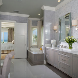 Photo of an expansive nautical ensuite bathroom in Orlando with a submerged sink, recessed-panel cabinets, grey cabinets, a built-in bath, grey tiles, white tiles, mosaic tiles, grey walls, porcelain flooring, marble worktops and white floors.