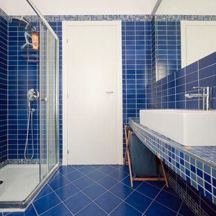 This is an example of a small mediterranean ensuite bathroom in Milan with a console sink, tiled worktops, a corner shower, a wall mounted toilet, blue tiles, porcelain tiles, blue walls and porcelain flooring.