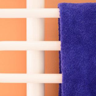 Modern inredning av ett mellanstort badrum med dusch, med ett väggmonterat handfat, släta luckor, vita skåp, en dusch i en alkov, en vägghängd toalettstol, vit kakel, keramikplattor och röda väggar