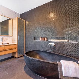 Immagine di una grande stanza da bagno padronale minimal con ante con riquadro incassato, ante in legno chiaro, vasca freestanding, doccia doppia, piastrelle a mosaico, lavabo a bacinella, top in superficie solida, piastrelle nere e pareti nere