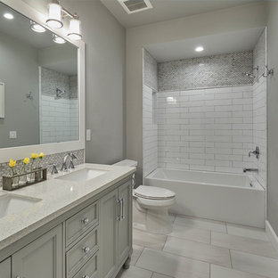 Mid-sized arts and crafts kids' multicolored tile and glass tile porcelain tile and gray floor tub/shower combo photo in Portland with shaker cabinets, white cabinets, a one-piece toilet, gray walls and an undermount sink