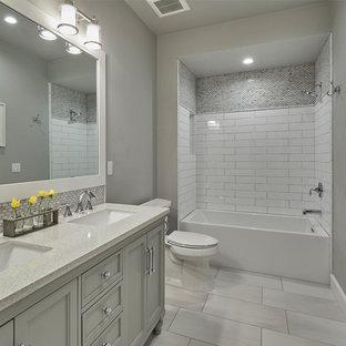 Foto di una stanza da bagno per bambini stile americano di medie dimensioni con ante in stile shaker, ante bianche, vasca/doccia, WC monopezzo, piastrelle multicolore, piastrelle di vetro, pareti grigie, pavimento in gres porcellanato, lavabo sottopiano e pavimento grigio