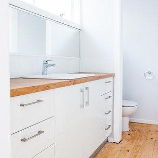 Foto di una stanza da bagno classica di medie dimensioni con nessun'anta, ante bianche, WC monopezzo, piastrelle bianche, piastrelle di cemento, pareti bianche, parquet chiaro, lavabo da incasso e top in legno