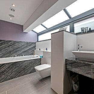 Mittelgroßes Modernes Badezimmer mit flächenbündigen Schrankfronten, schwarzen Schränken, Badewanne in Nische, Duschbadewanne, lila Wandfarbe, Aufsatzwaschbecken, Marmor-Waschbecken/Waschtisch, grauem Boden und schwarzer Waschtischplatte in Hertfordshire