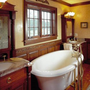 Imagen de cuarto de baño principal, tradicional, de tamaño medio, con lavabo tipo consola, armarios con paneles con relieve, puertas de armario de madera en tonos medios, encimera de ónix, bañera con patas, paredes amarillas y suelo de madera en tonos medios