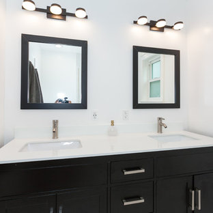 Example of a mid-sized minimalist 3/4 white tile and subway tile porcelain tile and white floor corner shower design in Los Angeles with beaded inset cabinets, dark wood cabinets, a one-piece toilet, white walls, a drop-in sink, quartz countertops, a hinged shower door and white countertops