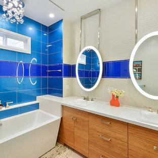 Imagen de cuarto de baño principal, contemporáneo, de tamaño medio, con armarios con paneles lisos, puertas de armario de madera clara, baldosas y/o azulejos azules, baldosas y/o azulejos de vidrio, suelo de baldosas tipo guijarro, lavabo integrado, encimera de acrílico, bañera exenta y paredes multicolor