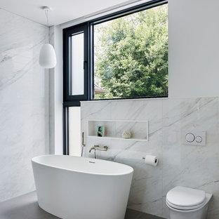 Immagine di una stanza da bagno padronale design con vasca freestanding, WC sospeso, pareti bianche, pavimento grigio, zona vasca/doccia separata, piastrelle grigie, piastrelle bianche e piastrelle di marmo
