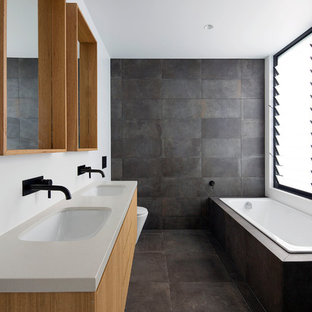 This is an example of a large contemporary kids bathroom in Sydney with flat-panel cabinets, medium wood cabinets, a drop-in tub, an open shower, a one-piece toilet, gray tile, ceramic tile, ceramic floors, an undermount sink, engineered quartz benchtops, grey floor and white benchtops.