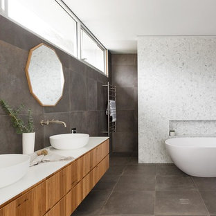 Photo of a large contemporary master wet room bathroom in Sydney with medium wood cabinets, a freestanding tub, a one-piece toilet, gray tile, marble, grey walls, porcelain floors, a vessel sink, black floor, an open shower and white benchtops.
