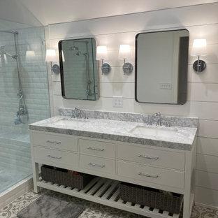 Bild på ett stort vintage grå grått en-suite badrum, med luckor med infälld panel, vita skåp, ett badkar med tassar, en dubbeldusch, ett urinoar, vita väggar, klinkergolv i porslin, ett undermonterad handfat, marmorbänkskiva och dusch med gångjärnsdörr