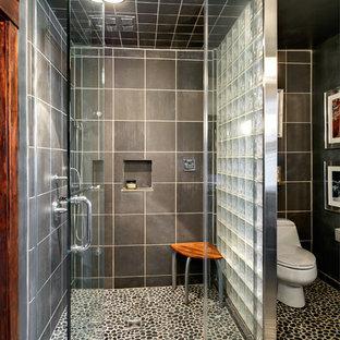 Modelo de cuarto de baño principal, bohemio, de tamaño medio, con armarios abiertos, suelo de baldosas tipo guijarro, paredes grises, suelo de baldosas tipo guijarro, lavabo bajoencimera, encimera de vidrio, ducha empotrada, sanitario de una pieza, baldosas y/o azulejos negros y baldosas y/o azulejos grises