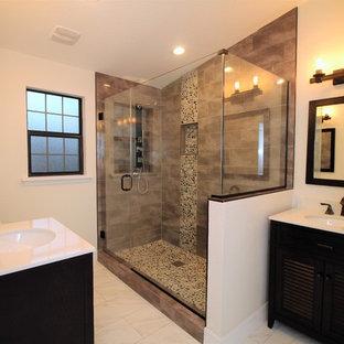 Стильный дизайн: ванная комната среднего размера в стиле современная классика с фасадами с филенкой типа жалюзи, черными фасадами, отдельно стоящей ванной, душем в нише, серой плиткой, керамогранитной плиткой, бежевыми стенами, полом из керамогранита, душевой кабиной, врезной раковиной, столешницей из искусственного камня, белым полом, душем с распашными дверями и белой столешницей - последний тренд