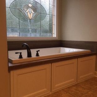 他の地域の中サイズのトラディショナルスタイルのおしゃれなマスターバスルーム (レイズドパネル扉のキャビネット、茶色いキャビネット、ドロップイン型浴槽、アルコーブ型シャワー、分離型トイレ、茶色いタイル、磁器タイル、グレーの壁、磁器タイルの床、アンダーカウンター洗面器、クオーツストーンの洗面台、茶色い床、開き戸のシャワー) の写真
