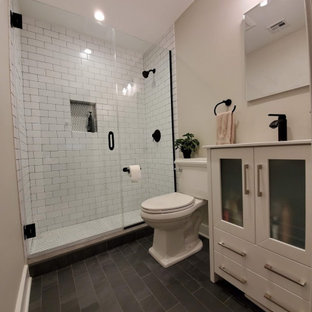 Example of a small eclectic master white tile and ceramic tile slate floor and gray floor alcove shower design in Philadelphia with shaker cabinets, white cabinets, beige walls, an integrated sink, solid surface countertops, a hinged shower door and white countertops