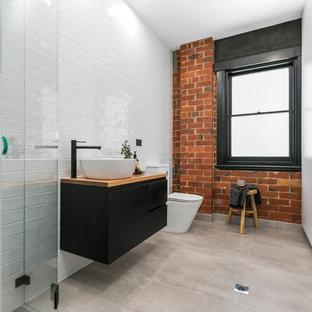 Réalisation d'une salle d'eau design avec un placard à porte plane, des portes de placard noires, un carrelage blanc, un carrelage métro, un mur blanc, une vasque, un plan de toilette en bois, un sol gris et buanderie.