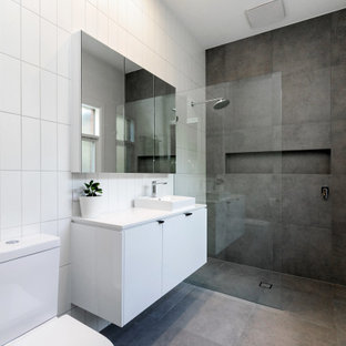 Design ideas for a contemporary 3/4 bathroom in Adelaide with flat-panel cabinets, white cabinets, a curbless shower, a two-piece toilet, gray tile, white walls, concrete floors, a vessel sink, grey floor, an open shower, white benchtops, a niche, a single vanity and a floating vanity.