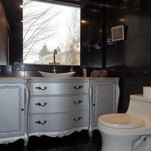Foto de cuarto de baño principal, de estilo zen, grande, sin sin inodoro, con armarios tipo mueble, puertas de armario grises, bañera exenta, baldosas y/o azulejos negros, paredes grises y lavabo sobreencimera