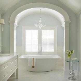 Modelo de cuarto de baño tradicional con lavabo bajoencimera, armarios tipo mueble, puertas de armario blancas, bañera exenta, paredes azules, suelo de mármol, baldosas y/o azulejos de piedra y encimera de mármol