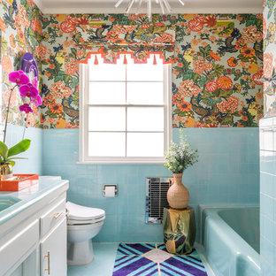 Exotisk inredning av ett blå blått badrum, med släta luckor, vita skåp, ett badkar i en alkov, flerfärgade väggar, kaklad bänkskiva och blått golv