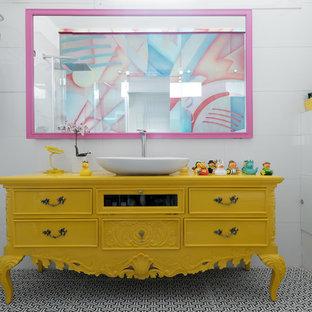 Idéer för ett eklektiskt gul badrum, med möbel-liknande, gula skåp, vit kakel, vita väggar, ett fristående handfat, träbänkskiva och flerfärgat golv