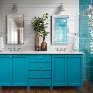 Design ideas for a beach style master wet room bathroom in Seattle with shaker cabinets, turquoise cabinets, a freestanding tub, blue tile, subway tile, white walls, dark hardwood floors, an undermount sink, brown floor, white benchtops and a sliding shower screen.