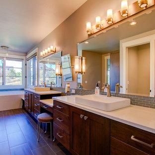Immagine di una grande stanza da bagno padronale shabby-chic style con ante lisce, ante in legno scuro, vasca da incasso, piastrelle grigie, piastrelle di vetro, pareti beige, pavimento in gres porcellanato, lavabo a bacinella, top in quarzo composito e pavimento marrone