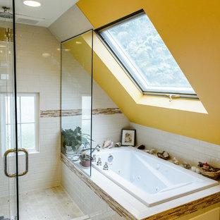 Modelo de cuarto de baño principal, actual, de tamaño medio, con bañera encastrada, ducha esquinera, baldosas y/o azulejos blancos, baldosas y/o azulejos de cemento, paredes amarillas, suelo de baldosas de porcelana y lavabo con pedestal