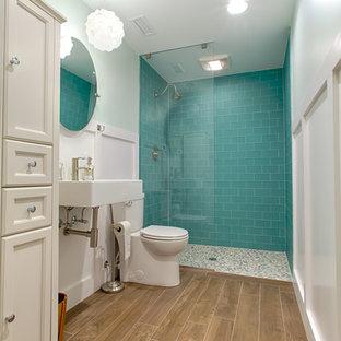 Foto di una stanza da bagno stile marinaro di medie dimensioni con doccia a filo pavimento, piastrelle blu, piastrelle di vetro, pavimento con piastrelle in ceramica, lavabo sospeso, pavimento marrone e doccia aperta