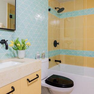 Diseño de cuarto de baño infantil, actual, pequeño, con puertas de armario amarillas, combinación de ducha y bañera, baldosas y/o azulejos multicolor, baldosas y/o azulejos de cerámica, paredes azules, suelo de madera clara, suelo beige, ducha abierta y encimeras amarillas