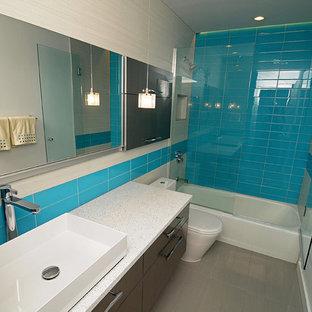 Imagen de cuarto de baño con ducha, contemporáneo, pequeño, con lavabo sobreencimera, armarios con paneles lisos, puertas de armario grises, encimera de cuarzo compacto, bañera empotrada, combinación de ducha y bañera, sanitario de una pieza, baldosas y/o azulejos grises, baldosas y/o azulejos de porcelana, paredes grises y suelo de baldosas de porcelana