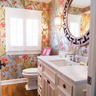 Ispirazione per una stanza da bagno con doccia classica di medie dimensioni con top in marmo, ante a filo, ante gialle, WC a due pezzi, pareti multicolore, parquet scuro, lavabo sottopiano e pavimento marrone