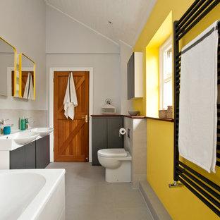 Modernes Kinderbad mit flächenbündigen Schrankfronten, grauen Schränken, Einbaubadewanne, Toilette mit Aufsatzspülkasten, gelber Wandfarbe und Einbauwaschbecken in Oxfordshire