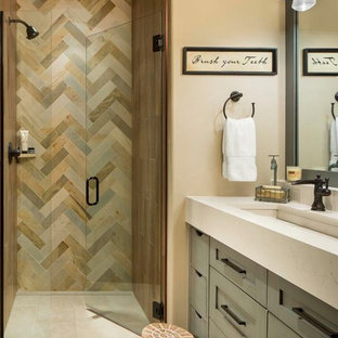 Alcove shower - mid-sized rustic master slate tile and multicolored tile porcelain floor and beige floor alcove shower idea in Denver with shaker cabinets, beige walls, engineered quartz countertops, a hinged shower door, beige countertops, gray cabinets and a trough sink
